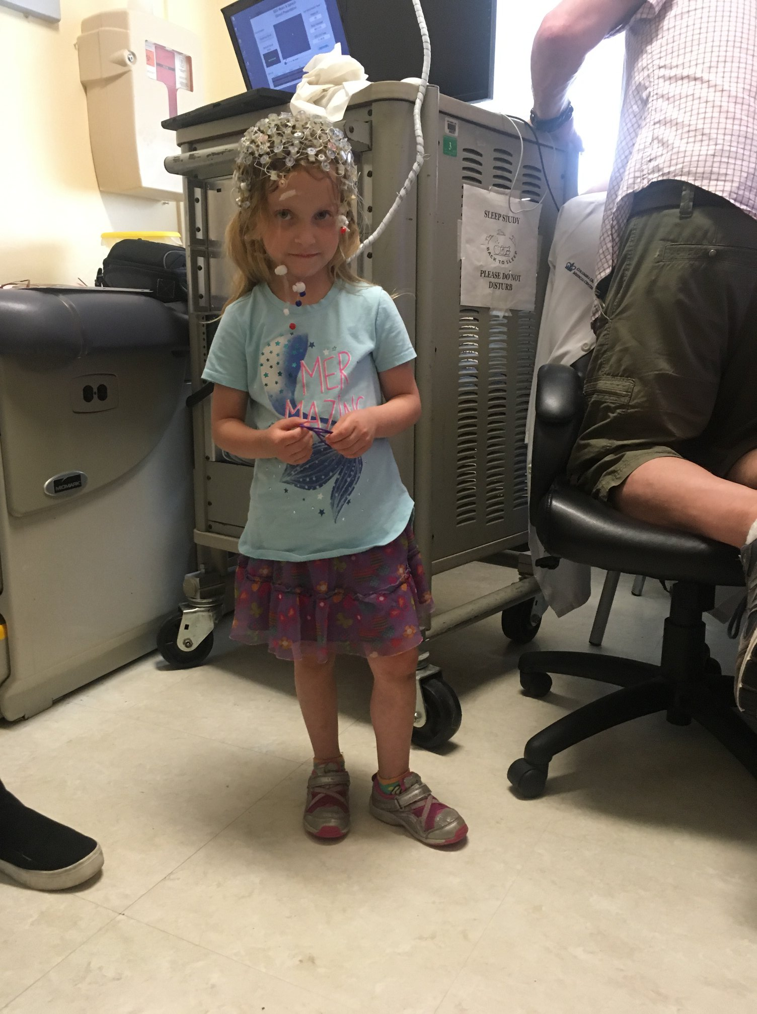 The child is equipped with an EEG cap that is connected to a machine that processes the activity on the scalp while the child listens to music.