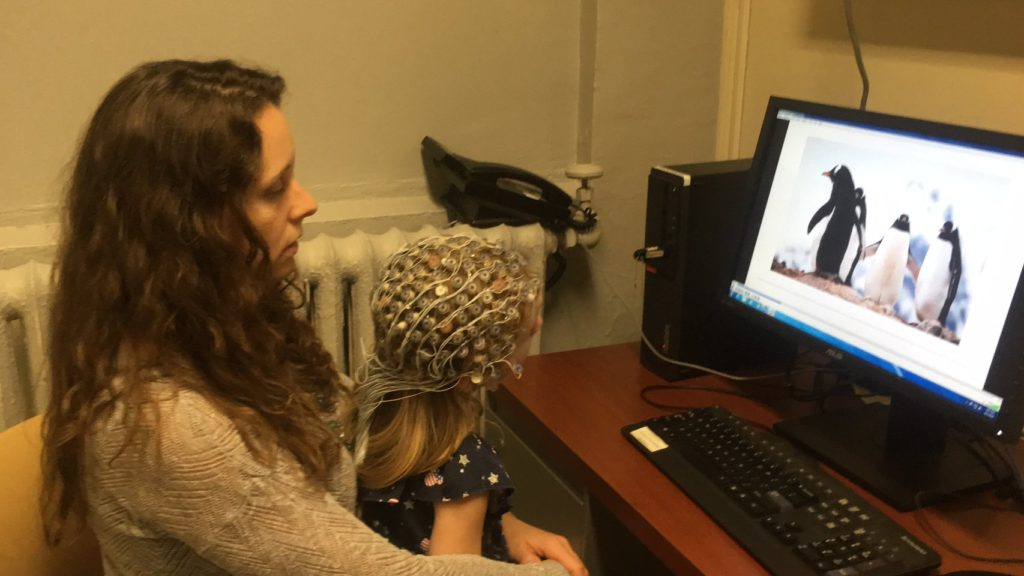Receptive language skills were assessed using an EEG with music paradigm. Pictured here: the child wears the EEG cap while listening to familiar children's songs, spoken versions of the same songs, and silence. Throughout the three sequences, the child watches images on a screen.